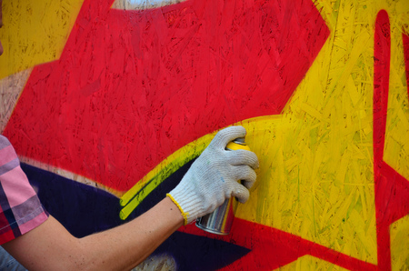 A hand with a spray can that draws a new graffiti on the wall. Photo of the process of drawing a graffiti on a wooden wall close-up. The concept of street art and illegal vandalism