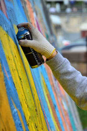 A hand with a spray can that draws a new graffiti on the wall. Photo of the process of drawing a graffiti on a concrete wall close-up. The concept of street art and illegal vandalism