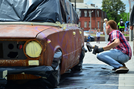 A young red-haired graffiti artist paints a new colorful graffiti on the car. Photo of the process of drawing a graffiti on a car close-up. The concept of street art and illegal vandalism