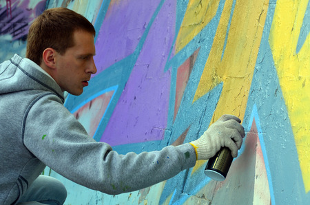 A young red-haired graffiti artist paints a new graffiti on the wall. Photo of the process of drawing a graffiti on a wall close-up. The concept of street art and illegal vandalism