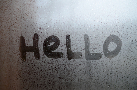The English word Hello is written with a finger on the surface of the misted glass Stock Photo