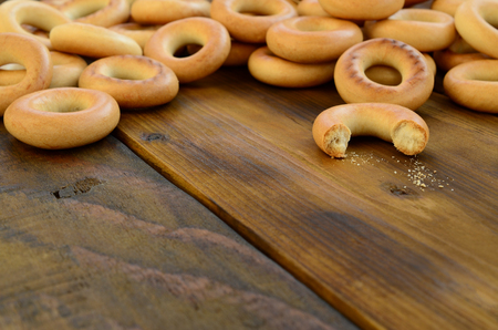 A lot of fresh yellow bagels lie on the surface of the old dark wood. A popular kind of flour products. One of the traditional Russian treats for tea