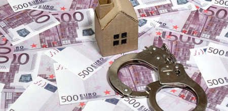Scam with real estate. Cheating when buying or renting a house. Punishment for deception. A toy house with handcuffs on a many 500 purple euro banknotes Stock Photo