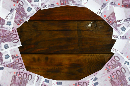 A lot of purple denominations worth 500 euros lie on a wooden surface with an empty pad in the middle of the image. Copy space for text