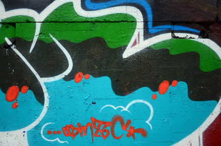 A fragment of graffiti drawing using contours, applied to the wall with the help of cans with aerosol paints over the colored filling areas. Background texture of street art and vandalism Stock Photo