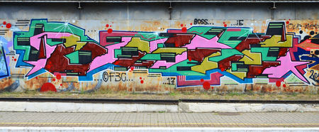 Background image with graffiti elements. Texture of the wall, painted in different colors of in the graffiti style. Concept of street culture, youth entertainment and illegal hooliganism
