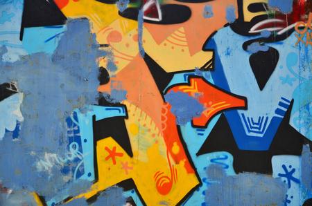 Die alte Wand, gemalt in den Farbgraffiti, die blaue Aerosolfarben zeichnen. Hintergrund auf dem Thema der Zeichnungsgraffiti und der Straßenkunst