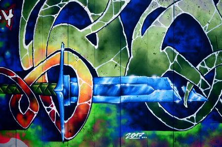 A fragment of detailed graffiti of a drawing made with aerosol paints on a wall of concrete tiles. Background image of street art with a fairy-tale crystal sword Stock Photo