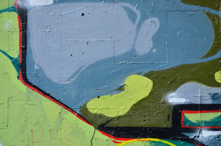 Fragment of an old colored graffiti drawing on the wall. Background image as an illustration of street art, vandalism and wall painting with aerosol paint
