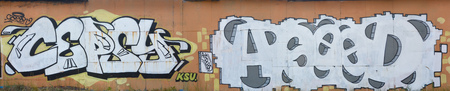 A photo of several graffiti artworks on the metal wall. Graffiti drawings are made with white paint with black outlines and have an orange background. Texture of wall with graffiti decoration Stock Photo