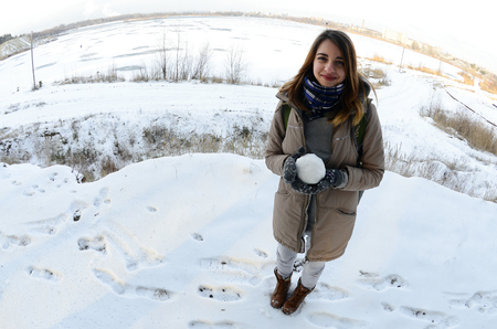 A young and joyful Caucasian girl in a brown coat holds a snowball in front of a horizon line between the sky and a frozen lake in winter. Fisheye Photo
