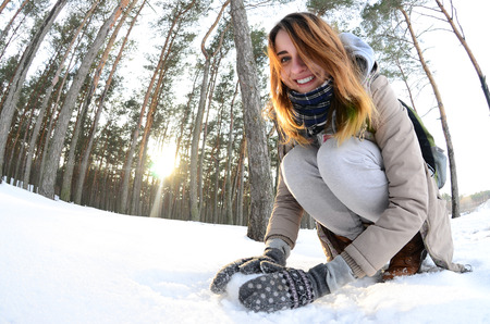 A young and joyful Caucasian girl in a brown coat sculpts a snowball in a snow-covered forest in winter. Games with snow in the open air. Fisheye Photo Stock Photo