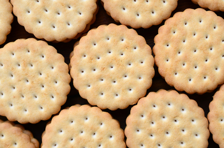 Detailed picture of round sandwich cookies with coconut filling. Background image of a close-up of several treats for tea