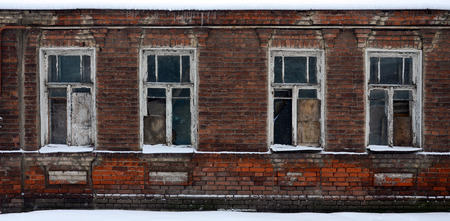 An old brick wall of an apartment house with a lot of boarded up windows without glass