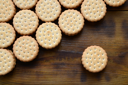 A round sandwich cookie with coconut filling lies in large quantities on a brown wooden surface. Photo of edible treats on a wooden background with copy space