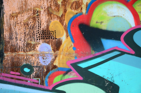 Close-up fragment of a graffiti drawing applied to the wall by aerosol paint. Background image of a modern composition of lines and colored areas. Street art concept