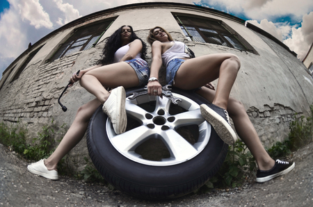 Bottom view of two young and sexy girls in light t-shirts and blue denim shorts with wheel wrenches are sitting on the big and silvery car wheel