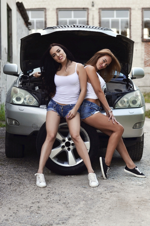 Two young and sexy caucasian girls (blonde and brunette) with wheel wrenches around a big silvery off-road car with an open hood. The concept of repair and maintenance of a car