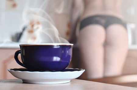 Dark blue cup of hot tea with steam on a white saucer. On blurred background girl in black lingerie near a kitchen counter. The concept of tea party at home