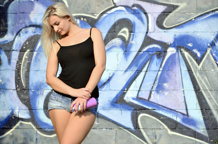 A young and beautiful sexy girl graffiti artist with a paint spray stands on the wall background with a graffiti pattern in blue and purple tones Standard-Bild - 96481868