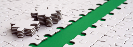 The green path is laid on the platform of a white folded jigsaw puzzle. The missing elements of the puzzle are stacked nearby. Texture image with space for text Stock Photo