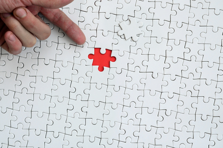 The texture of a white jigsaw puzzle in the assembled state with one missing element, forming a red space, pointed to by the finger of the male hand Stock Photo