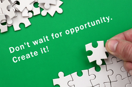 Don't wait for opportunity. Create it. The hand folds a white jigsaw puzzle and a pile of uncombed puzzle pieces lies against the background of the green surface