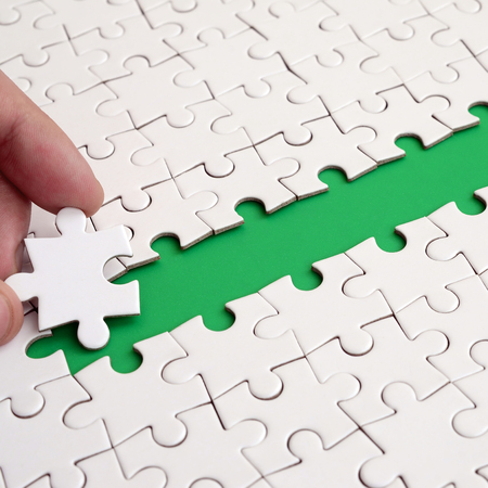 The human hand paves the way to the surface of the jigsaw puzzle, forming a green space. The concept of overcoming the difficulties on the way to success Stock fotó