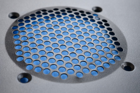 Close-up, shallow focus of a meshed style cooling panel used on a main frame computer. The circular holes aid active venting of hot air within the computer