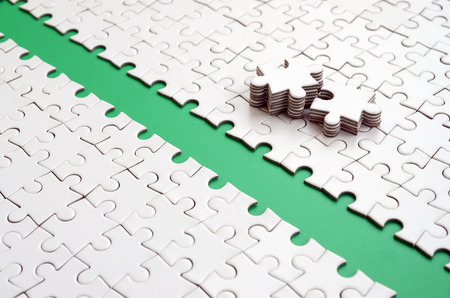 The green path is laid on the platform of a white folded jigsaw puzzle. The missing elements of the puzzle are stacked nearby. Texture image with space for text Stock fotó