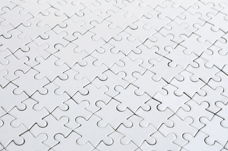 Close up of a white jigsaw puzzle in assembled state in perspective. Many components of a large whole mosaic are united Stock Photo