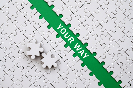 Your way. The green path is laid on the platform of a white folded jigsaw puzzle. The missing elements of the puzzle are stacked nearby