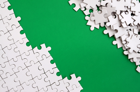 Fragment of a folded white jigsaw puzzle and a pile of uncombed puzzle elements against the background of a green surface. Texture photo with space for text