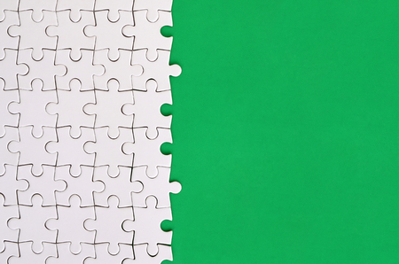 Fragment of a folded white jigsaw puzzle on the background of a green plastic surface. Texture photo with copy space for text