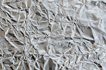Thin wrinkled sheet of crushed tin aluminum silver foil background with shiny crumpled surface for texture Reklamní fotografie