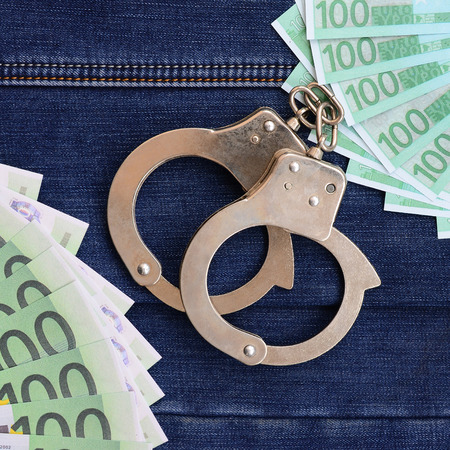 The fan of a lot of euro bills and police handcuffs is on a dark denim surface. Background image Stock Photo