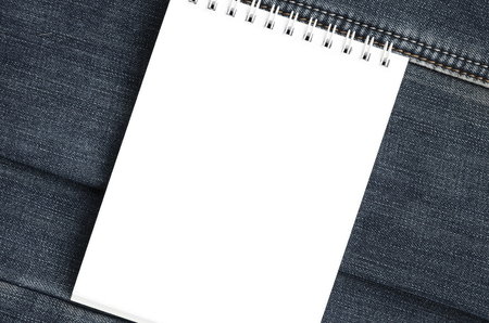 White notebook with clean pages lying on dark blue jeans background. Image with copy space Stock Photo