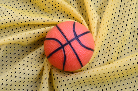 Small orange rubber basketball lies on a yellow sport jersey clothing fabric texture and background with many folds Stock Photo