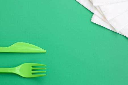 Disposable plastic cutlery green. Plastic fork and knife lie on a green background surface next to napkins