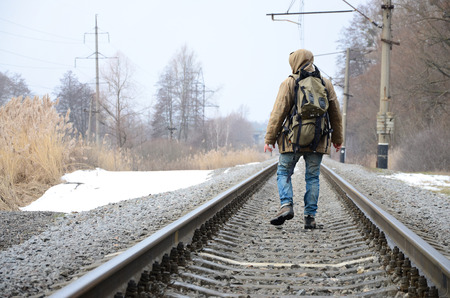A man with a large backpack goes ahead on the railway track during the winter season Stock Photo