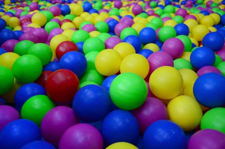 Beaucoup de boules en plastique colorées dans un ballon pour enfants sur une aire de jeux. Modèle de gros plan