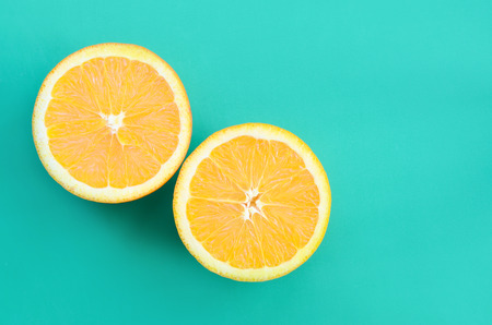 Top view of a several orange fruit slices on bright background in turquoise green color. A saturated citrus texture image