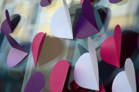 A lot of pink, purple and white paper hearts decorate the window of the house Stock Photo