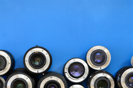 Several photographic lenses lie on a bright blue background. Space for text Stock Photo