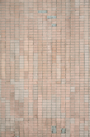 Old Soviet beige wall tiles. The texture of the classical outer tile, which was revetted by buildings during the times of the Soviet Union Foto de archivo