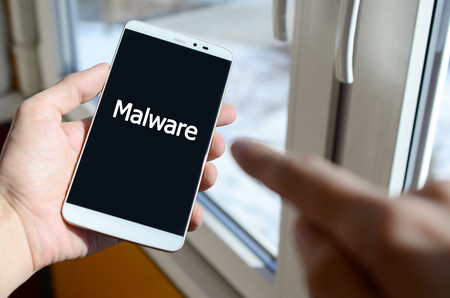A person sees a white inscription on a black smartphone display that holds in his hand. Malware Stock Photo