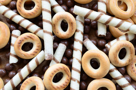 A lot of crispy sweet tubules, chocolate melting balls and yellow bagels lie on a wooden surface. Close up view