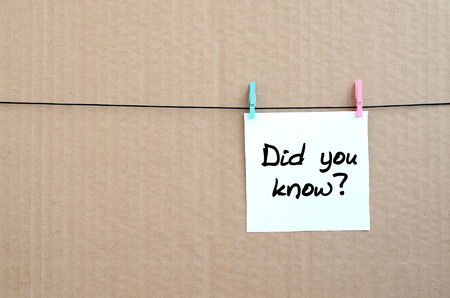 Did you know? Note is written on a white sticker that hangs with a clothespin on a rope on a background of brown cardboard