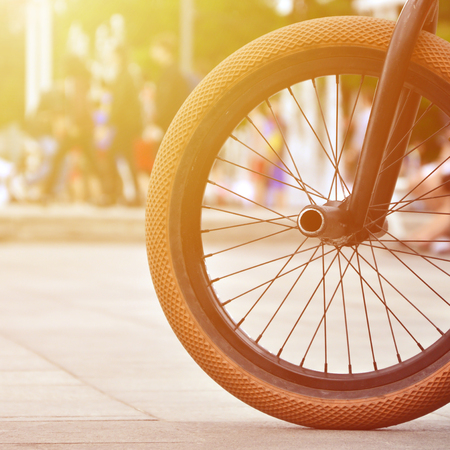 A BMX bike wheel against the backdrop of a blurred street with cycling riders. Extreme Sports Concept Stock Photo