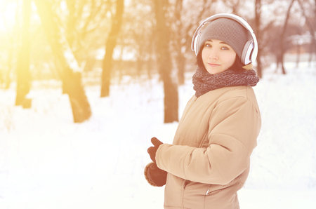 Portrait of pretty attractive caucasian pierced girl hipster winter park. She is listening to music on headphones. Youth street fashion. Winter fun.  Walks in the open air